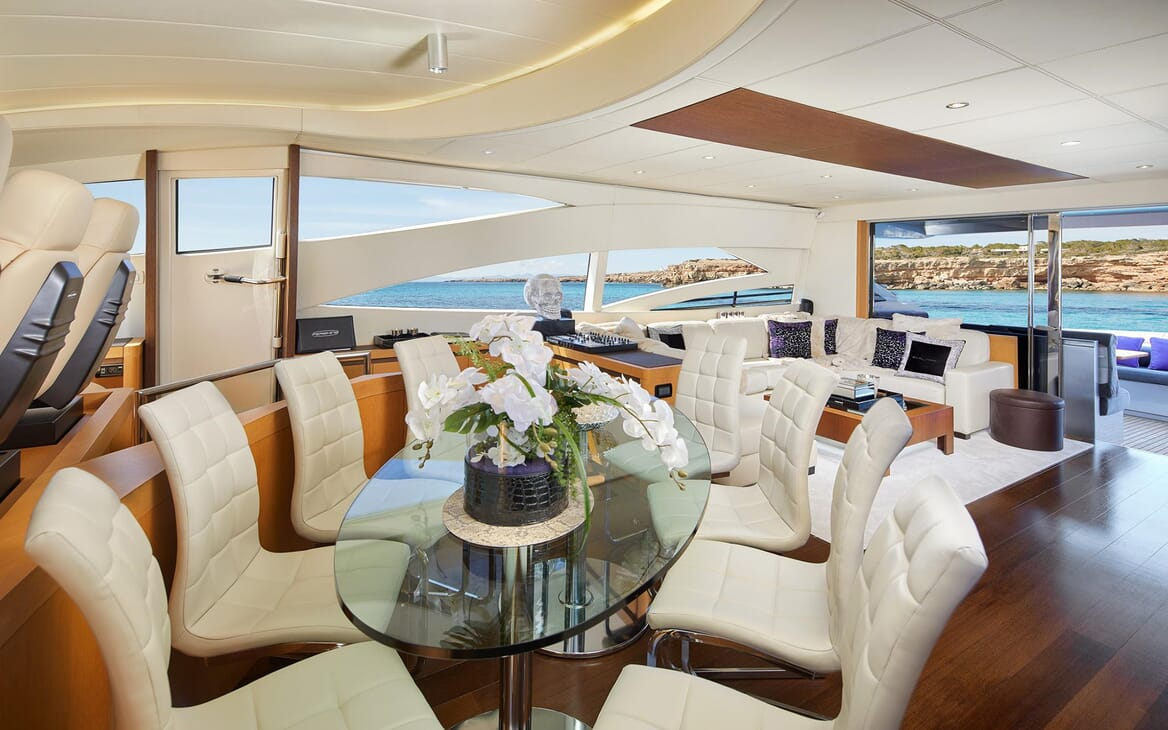 Motor Yacht SHALIMAR II dining area glass table with seating for eight behind cockpit