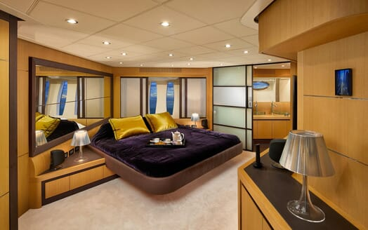Motor Yacht SHALIMAR II master suite with purple and mustard silk bed linen, mirrored walls and sliding frosted glass door to ensuite