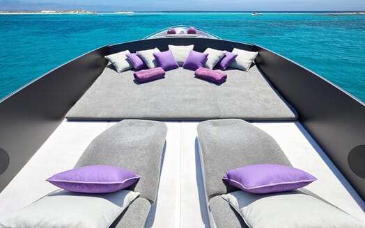 Motor Yacht SHALIMAR II bow lounge area with grey and purple furnishings and views of turquoise water