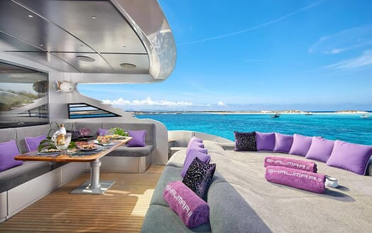 Motor Yacht SHALIMAR II deck area with grey and purple furnishings, views of turquoise water and alfresco dining area