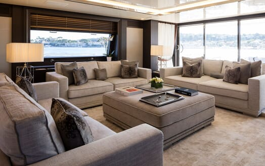 Motor yacht DOJO living area with soft grey furnishing and a large glass windows with sea views