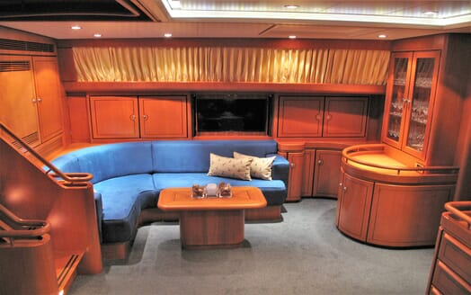 Sailing yacht SEA BREEZR seating area with blue cushions wood panelling and cabinets