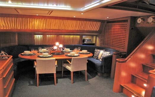 Sailing yacht SEA BREEZE dining area with table laid navy cushions