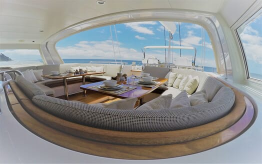 Sailing yacht SEA BREEZE outdoor undercover seating area with table setting and cushions