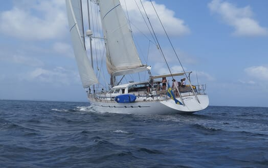 Sailing yacht SEA BREEZE stern shot on water with crew members