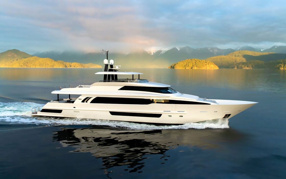 Motor yacht CRESCENT 117 hero shot on water with green landscape