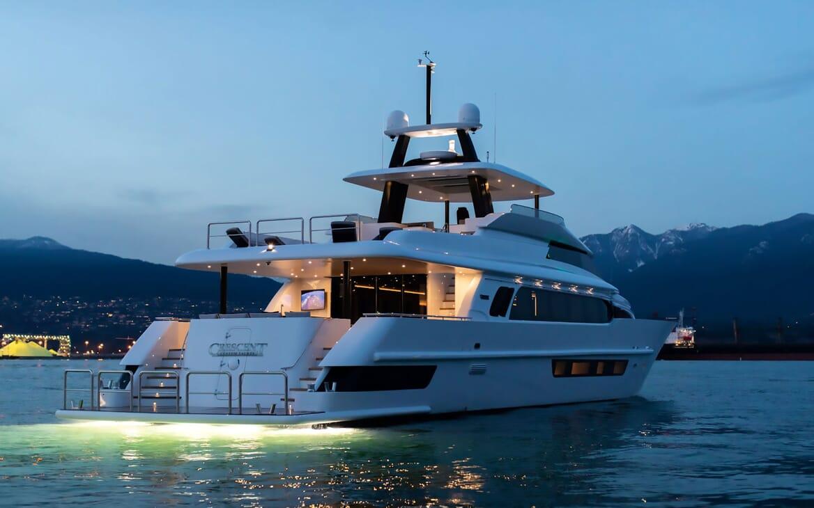 Motor yacht CRESCENT 117 hero aft shot at dusk with underwater lighting