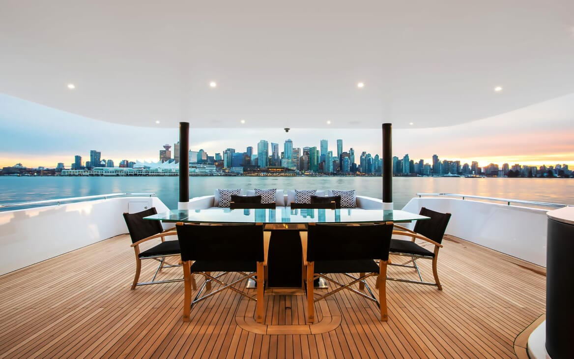 Motor yacht CRESCENT 117 deck with alfresco dining table for 6 with cityscape views