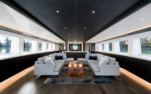 Motor yacht CRESCENT 117 contemporary living room with black ceiling, soft lighting and grey furnishings