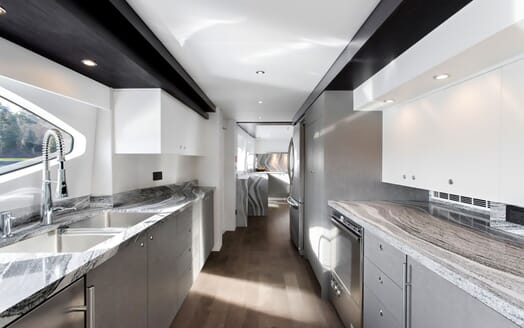 Motor yacht CRESCENT 117 kitchen with grey marble counter top, soft lighting and grey furnishings