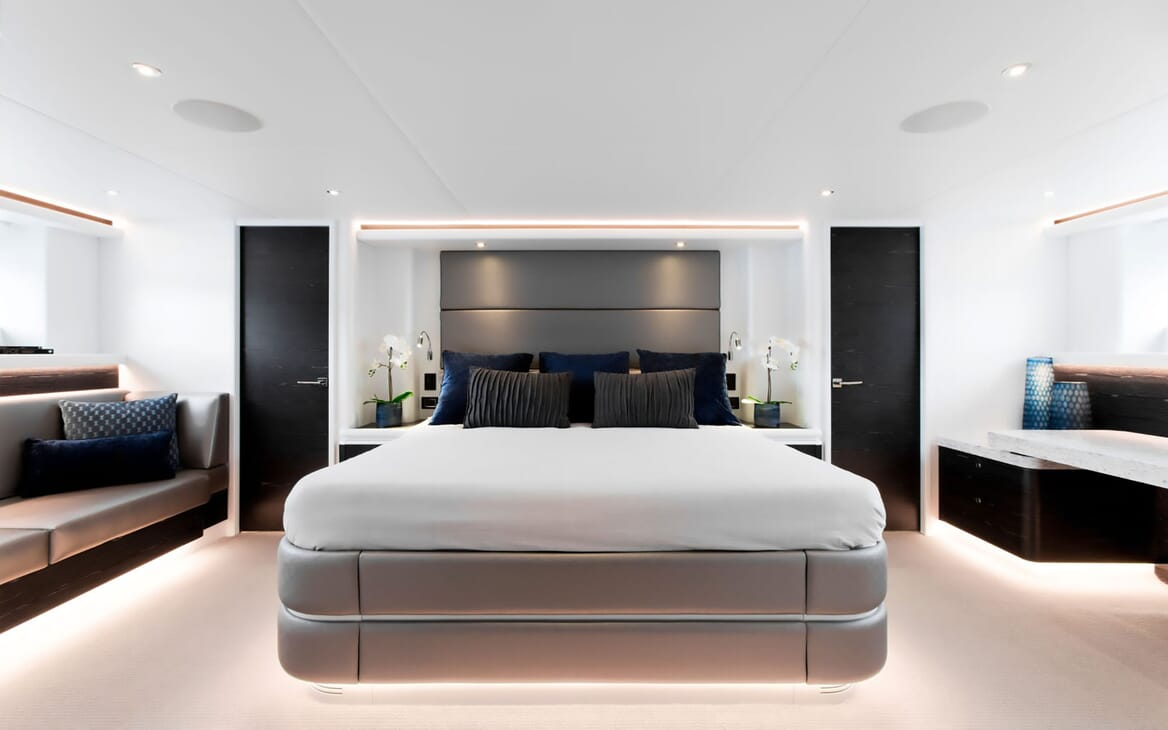 Motor yacht CRESCENT 117 master suite with king sized bed with white linen, soft lighting and grey furnishings