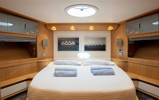 Motor Yacht SLIP AWAY master suite with wood surroundings, skylight and abstract marine artwork