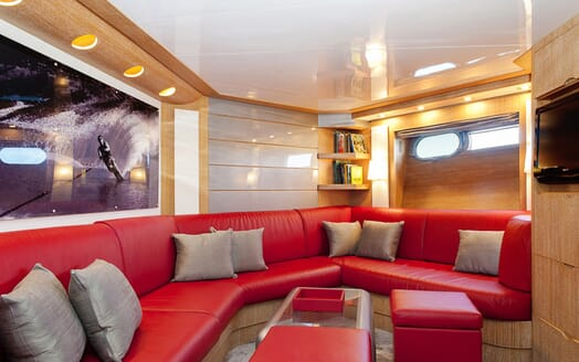 Motor Yacht SLIP AWAY lounge area with red leather seating, beech wood surroundings and small plasma TV