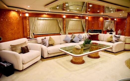 Motor yacht WHEELS I living room with large sofa and polished wood surroundings