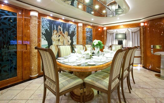 Motor yacht WHEELS I dining room with large mural painting