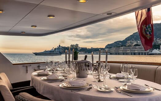 Motor yacht Superfun alfresco dining area with laid table and candles, views of monaco shoreline at dusk