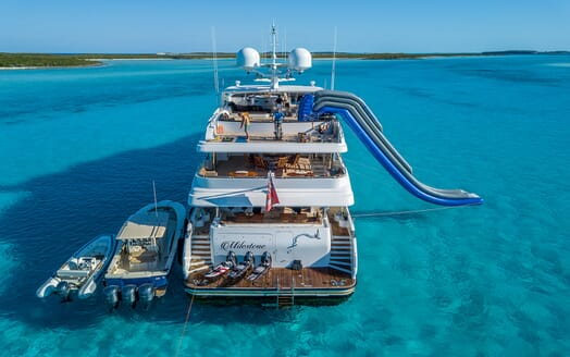 Motor yacht MILESTONE aft aerial shot on turquoise water and tender