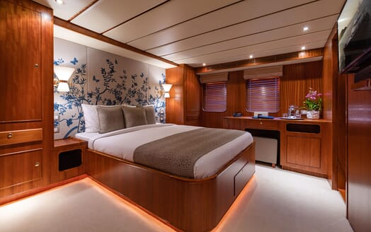 Motor yacht Northern Sun stateroom with white bed linen and mural wallpaper with dark wood desk