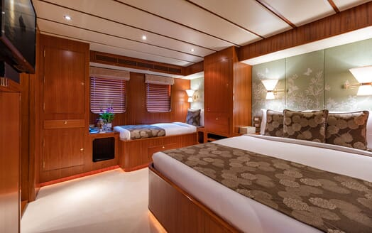 Motor yacht Northern Sun twin stateroom with green mural wallpaper and white bed linen and dimmed lighting