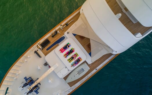 Motor yacht Northern Sun aerial shot of four people lying on colourful yoga mats on deck