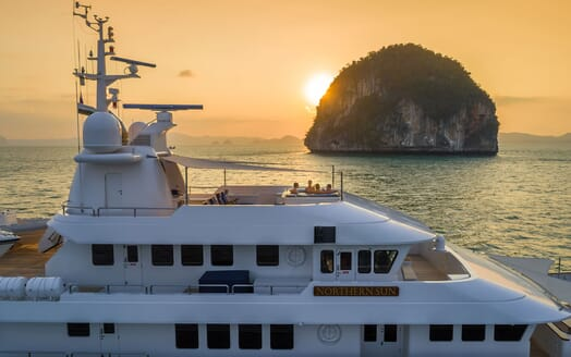 Motor yacht Northern Sun aerial hero shot at dusk with people in top deck jacuzzi
