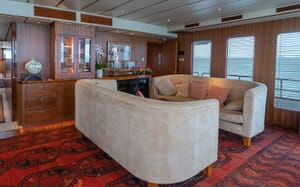 Motor yacht Northern Sun living room with red patterened carpet and two piece oatmeal sofa