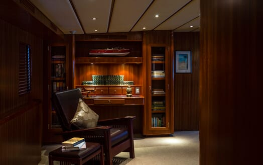 Motor yacht Northern Sun study with leather armchair, bookcase desk and varnished wood surroundings