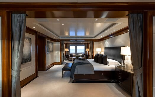 Motor Yacht SEANNA master suite with white linen, grey and dark wood furnishings and low lighting