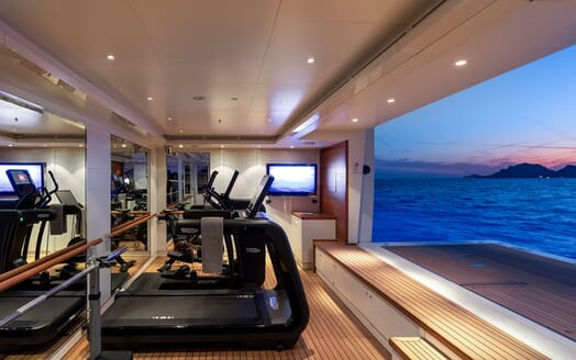 Motor Yacht SEANNA gym room with views out to beach club and water at dusk