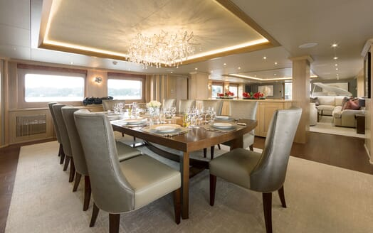 Motor yacht Minderella dining room with laid table and bespoke light fixture