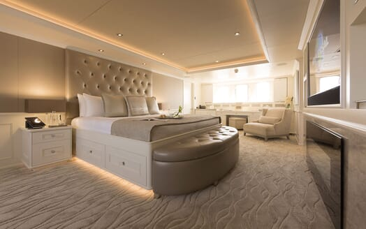 Motor yacht Minderella master suite with stone and white interiors, large headboard and plasma TV