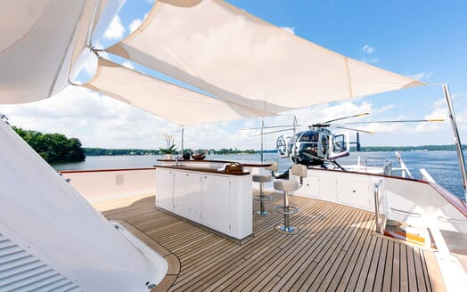 Motor yacht Minderella bar on deck with shade with helicopter in view