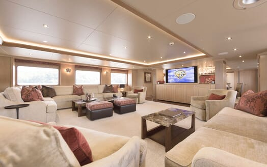 Motor Yacht Minderella living room with oatmeal soft two piece large sofas, large plasma screen and low ceiling lighting