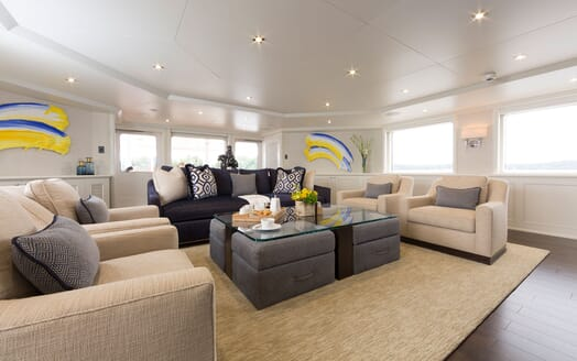 Motor Yacht Minderella living room with three piece sofa, large coffee table and dark wood floors