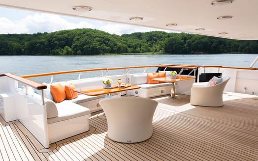 Motor Yacht Minderella deck with alfresco dining area with sea and forest views