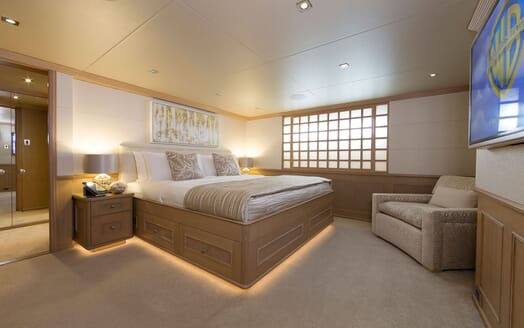 Motor Yacht Minderella master suite with king sized bed with gold and white bed linen and plasma TV