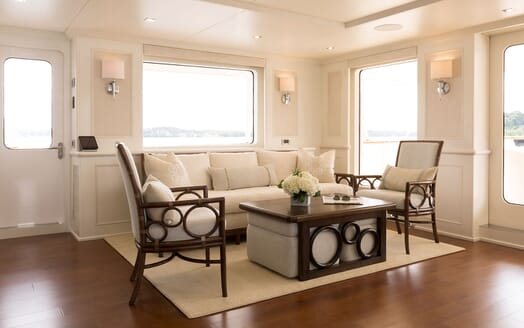 Motor Yacht Minderella seating area with cream sofa arm chairs, coffee table and white flowers